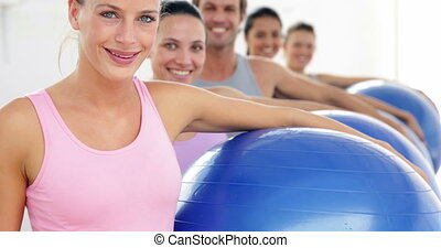 Fitness class holding exercise balls