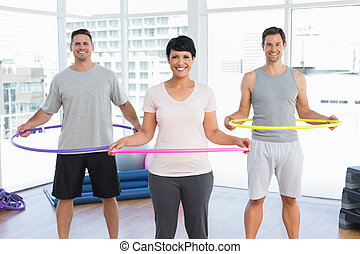 Fitness class holding hula hoops ar - Portrait of fitness ...
