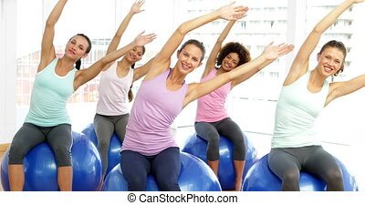 Fitness class in studio sitting on exercise balls