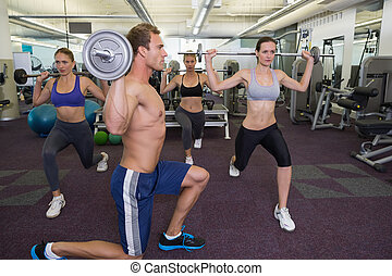 Fitness class lifting barbells together at the gym