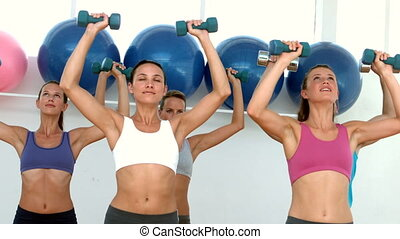 Fitness class lifting dumbbells