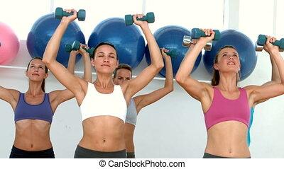 Fitness class lifting dumbbells