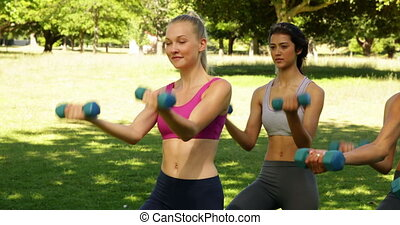 Fitness class lifting hand weights