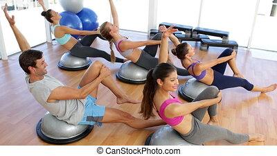 Fitness class lying on bosu balls t