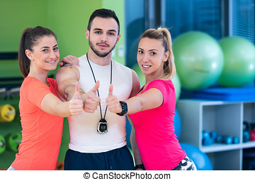 Fitness class showing thumbs up in gym