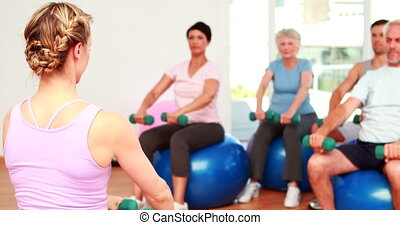 Fitness class sitting on exercise ball