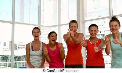 Fitness class smiling at camera showing thumbs up in slow ...