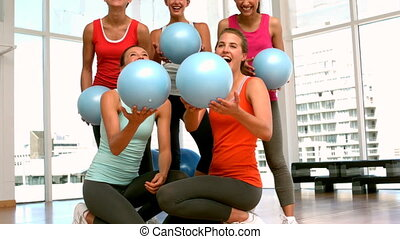 Fitness class throwing exercise balls