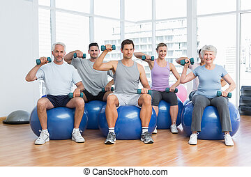 Fitness class with dumbbells sitting on exercise balls in gym