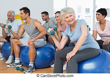 Fitness class with dumbbells sitting on exercise balls in...