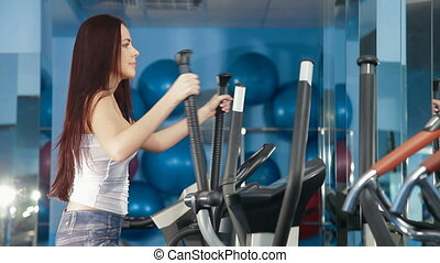 Fitness Club - Young Woman On Cross Trainer At The Gym...