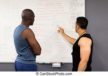 fitness coach planning gym session with client