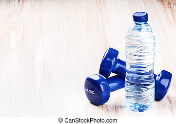 Fitness concept with dumbbells and bottle of water