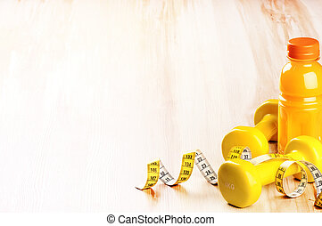 Fitness concept with dumbbells and fresh fruit juice