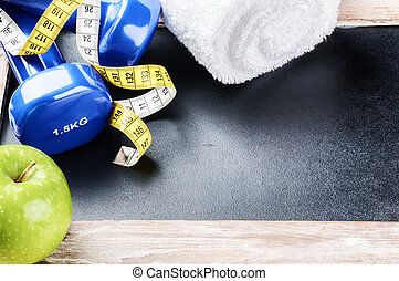 Fitness concept with dumbbells and green apple