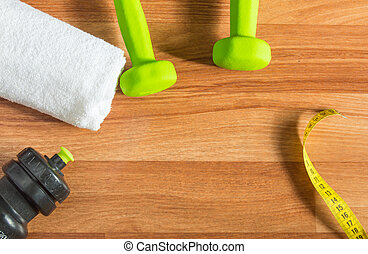 Fitness concept with dumbbells, water bottle, measuring tape, towel on wooden background