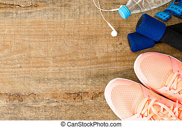 Fitness concept  with sneakers, dumbbells, water bottle and headphones on wooden background