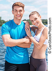 Fitness couple. Beautiful young couple in sports clothing standing together outdoors and smiling