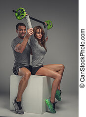 Fitness couple exercising with green barbell.