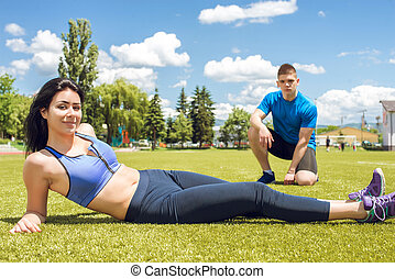 Fitness couple relaxing after training on grass.
