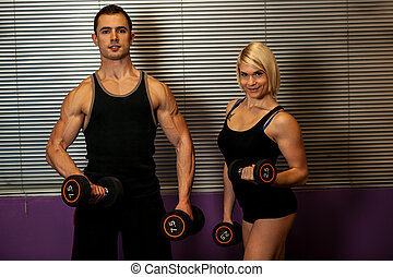 Fitness couple trains in gym with dumbbells