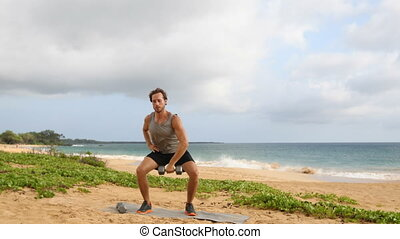 Fitness Dumbbell Snatch - man doing strength training exercises with Dumbbells on beach. Fit handsome male fitness model sweating during dumbbell workout exercise outdoors on beach. SLOW MOTION.