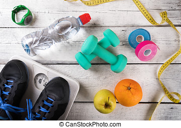 fitness equipment and accessories on white wood background. flat lay