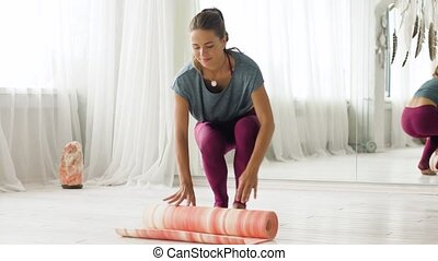 woman rolling up mat at yoga studio or gym - fitness...
