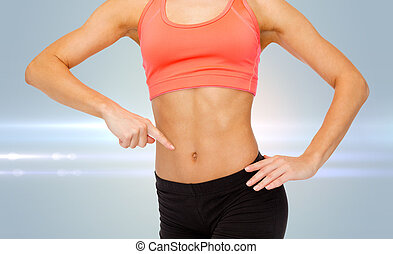 close up of woman pointing finger at her six pack - fitness...