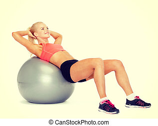 smiling sporty woman exercising on fitness ball