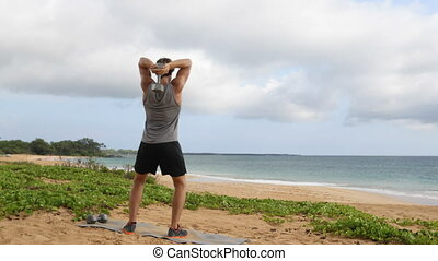 Fitness exercise with dumbbells - Man doing Standing Dumbbell Triceps Extension. Fit male fitness model doing workout exercises outside on beach.