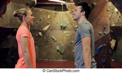 man and woman exercising at indoor climbing gym - fitness,...