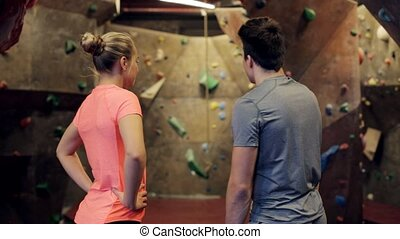 man and woman talking at indoor climbing gym - fitness,...
