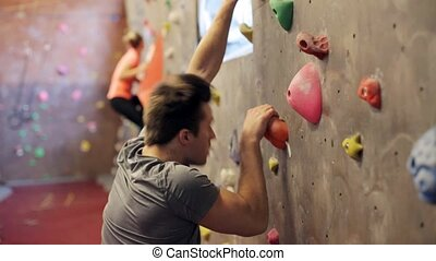young man exercising at indoor climbing gym wall - fitness,...