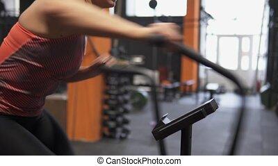 Fitness female doing air bike cross training in gym