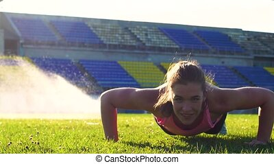 Fitness female doing pushups on green grass