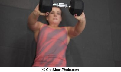Fitness female doing weighted sit-ups exercise in gym