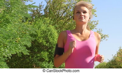 Fitness female runner in sporty pink top jogging in the park