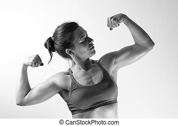 Fitness female showing biceps muscles.