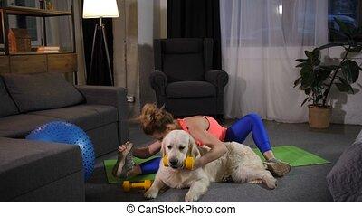 Fitness female stretching with retriever dog - Labrador pet...