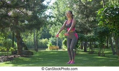 Fitness female with dumbbells squatting outdoors
