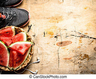 Fitness food. Chunks of watermelon with headphones and sneakers.