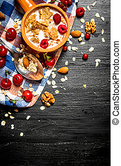 Muesli with berries, nuts and milk in the bowl.