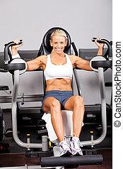 fitness, frau, gebrauchend, peck- plattform, maschine, in, turnhalle