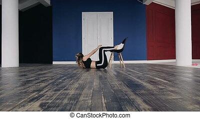 Fitness girl doing exercise press lying on floor leaning...