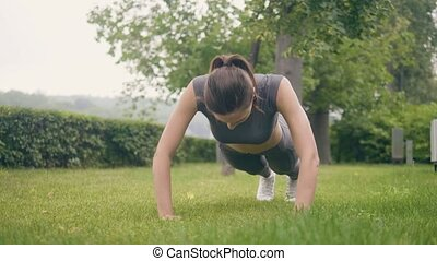 Fitness girl doing push ups exercises during outdoor training in summer park