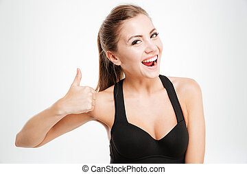 Fitness girl in sportwear showing thumbs up with one hand - ...