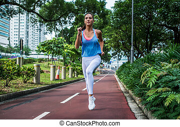 Fitness girl jogging on running path in the park in summer