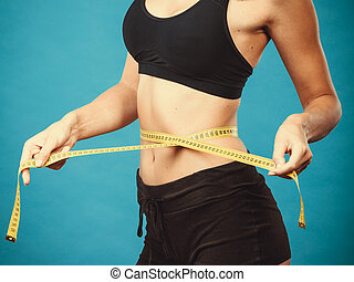 Fitness girl measuring her waistline - Weight loss, slim...