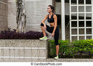 Fitness girl recovering after jogging or exercising outside in urban area, listening to music in earphones and looking into the distance